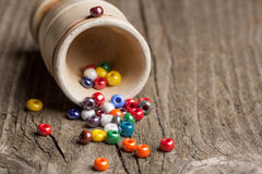 Colorful glass beads closeup. Colorful beautiful glass beads with ceramic glass on old wooden table Stock Photography