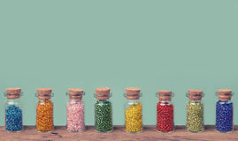 Colorful glass beads in a small bottles Royalty Free Stock Images