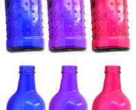 Colorful glass bottles. Blue, purple ad pink glass bottles shown in top and bottom halves Royalty Free Stock Photography