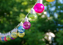 Colorful glass bulbs. Colorful vitreous bulbs. Lamps on wire Stock Images
