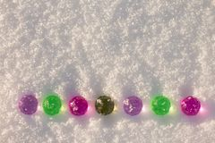 Colorful glass christmas balls on the shining snow background. stock photos