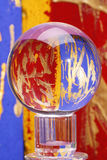Colorful glass crystal ball. Ball of crystal glass on pedestal of ground glass in front of abstract background. The colours of this, red, blue and gold are Royalty Free Stock Photos