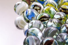 Colorful glass marbles. Some colorful marbles on a white surface stock images