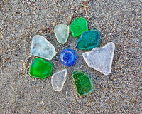 Colorful glass pieces on wet sand beach Stock Images