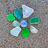 Colorful glass pieces on wet sand beach Royalty Free Stock Images