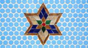 Colorful glass star decoration on blue wall Royalty Free Stock Image