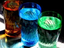 Colorful Glasses. Three color-tinted glasses filled with drinking water royalty free stock image