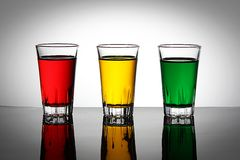 Colorful glasses of liquid. Three colorful glasses of liquid reflecting on light background Royalty Free Stock Image