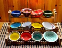 Colorful glazed bowls displayed on wooden stand Royalty Free Stock Photos