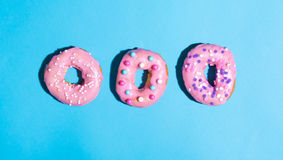 Colorful glazed donuts on a bright background Stock Images