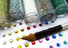 Colorful glitter and rhinestone crafts with brush. Colorful glitter bottles, rhinestones and a paintbrush arts and craft display Royalty Free Stock Photography