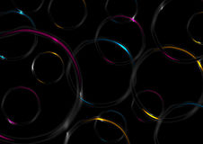 Colorful glossy glowing rings on black background Stock Image
