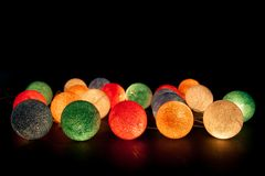 Colorful glowing balls on a black background. Glowing garland at night. Colorful circles on the background. Decorations for an apartment Royalty Free Stock Image