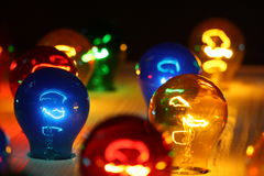 Colorful glowing bulbs. On a wooden surface royalty free stock photos