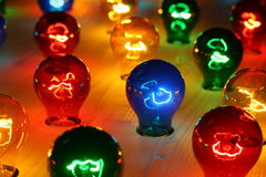 Colorful glowing bulbs. On a wooden surface royalty free stock images