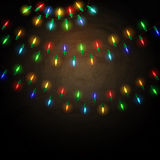 Colorful glowing christmas lights on blackboard background stock photos