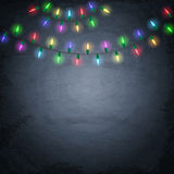 Colorful glowing christmas lights on chalkboard background Stock Images