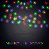 Colorful glowing christmas lights on chalkboard background Royalty Free Stock Image