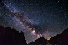 The colorful glowing core of the Milky Way and the starry sky captured at high altitude in summertime on the Alps. Scenic snowcapp Royalty Free Stock Photography