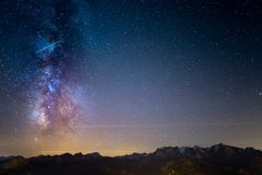 The colorful glowing Milky Way and the starry sky over the French Alps and the majestic Massif des Ecrins. The colorful glowing Milky Way and the starry sky Stock Photo