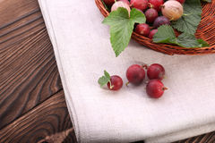 Colorful gooseberries in a basket on a wooden background. A few sweet gooseberries and fresh leaves on a light cloth. Nutrients. Royalty Free Stock Photography