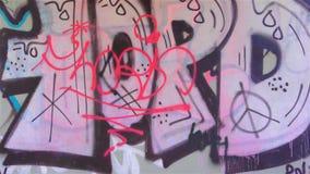 Colorful graffiti on a concrete bridge. Illegal Graffiti on the wall of the bridge stock footage