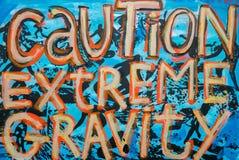 Colorful graffiti with message 'Caution Extreme Gravity', Lovina Stock Photos