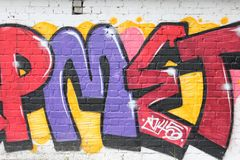 Colorful graffiti on a white brick wall royalty free stock images