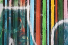 Colorful graffiti on wooden wall. Close-up view of a wooden wall with colorful vertical paint stripes and graffiti stock photos