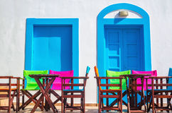 Colorful Greek restaurant table and chairs in front of iconic bl. Ue wooden doors and white walls in Greece Royalty Free Stock Photography