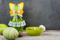 Colorful green easter eggs and lit candle Stock Photo