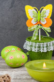 Colorful green easter eggs and lit candle Royalty Free Stock Photo