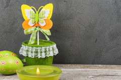 Colorful green easter eggs and lit candle Royalty Free Stock Images