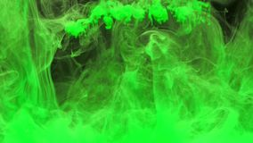 Colorful green ink drops from above mixing in water, swirling softly underwater with green ink on background. Colored acrylic cloud of paint isolated. Abstract stock video footage