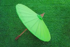 Colorful green oil paper umbrella with wood handle on green grass background royalty free stock photo