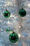 Colorful green ornaments and blinking lights on white Christmas tree Royalty Free Stock Photography