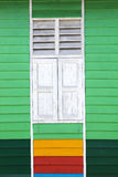 Colorful green wooden wall with white window Stock Photos