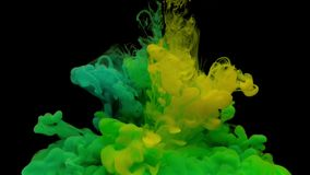 Colorful green and yellow ink drop from above mixing in water. Swirling softly underwater on black background. Acrylic cloud of paint isolated. Abstract smoke stock video footage
