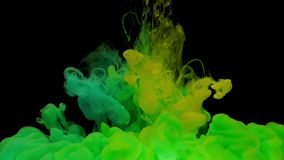 Colorful green and yellow ink mixing in water. Swirling softly underwater on black background with copy space. Colored acrylic cloud of paint isolated stock video footage