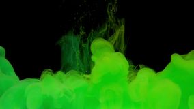 Colorful green and yellow ink mixing in water. Swirling softly underwater on black background with copy space. Colored acrylic cloud of paint isolated stock video