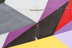 Colorful grey, purple, yellow, red and black painted wall with cracks. As background or texture Stock Photography