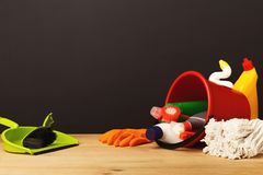 Colorful group of cleaning supplies. For natural and environmentally friendly cleaning. Bottles in pail, mop, scoop on wood table. House keeping, tidying up stock image
