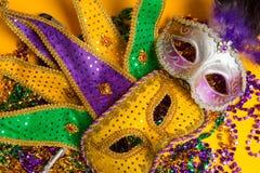 Colorful group of Mardi Gras or venetian mask on yellow. A festive, colorful group of mardi gras or carnivale mask on a yellow background. Venetian masks stock photos