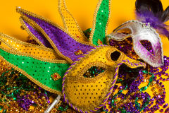 Colorful group of Mardi Gras or venetian mask on yellow. A festive, colorful group of mardi gras or carnivale mask on a yellow background. Venetian masks royalty free stock photo