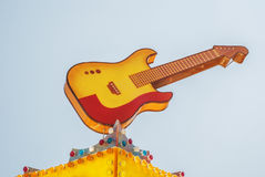 Colorful guitar at a fun fair. Amusement park Stock Photo