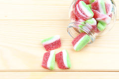 Colorful gummy candy in jars. Gummy candy in jars in the wood background Royalty Free Stock Image