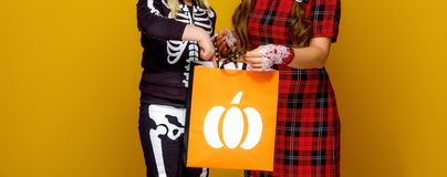 Happy modern mother and child looking at Halloween shopping bag Stock Image