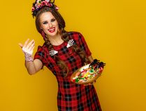 Woman with plate of Halloween candies calling to come closer. Colorful halloween. smiling modern woman in Mexican style halloween costume on yellow background stock photography