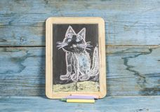 Colorful hand drawing with chalk on blackboard : funny cat. Colorful chalk drawing on blackboard : funny cat hand royalty free stock image