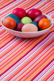 Colorful hand dyed easter eggs in a bowl on a table with striped Royalty Free Stock Photography